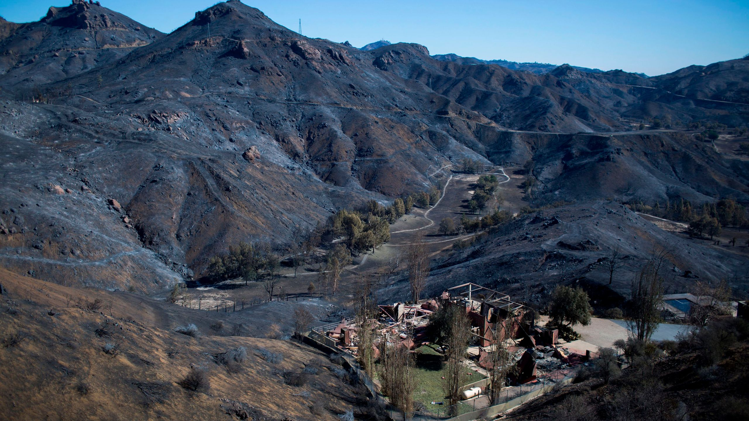 The Santa Monica Mountains are seen left blackened by the Woolsey Fire near Malibu on Nov. 14, 2018. (David McNew / AFP / Getty Images)