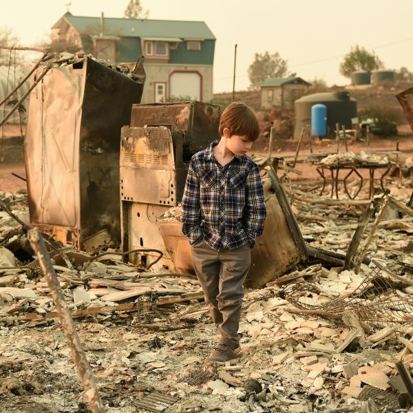 Jacob Saylors, 11, walks through the burned remains of his home in Paradise, Calif. on Nov. 18, 2018. The family lost a home in the same spot to a fire 10 years prior. (Credit: Josh Edelson / AFP) require. (Credit: JOSH EDELSON/AFP/Getty Images)