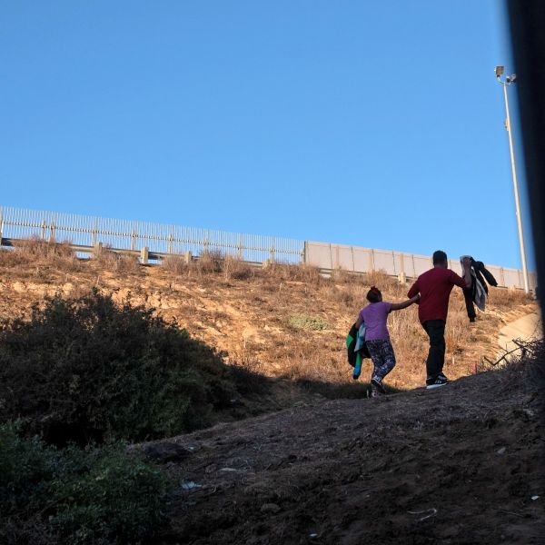 Honduran Andrea Nicolle, 10, and her father, Tony, traveling in a caravan of Central American migrants hoping to get to the United States, walk to surrender to the Border Patrol after crossing through a hole on the ground under the metal barrier separating Mexico and the U.S. on Dec. 4, 2018. (Credit: Guillermo Arias / AFP / Getty Images)