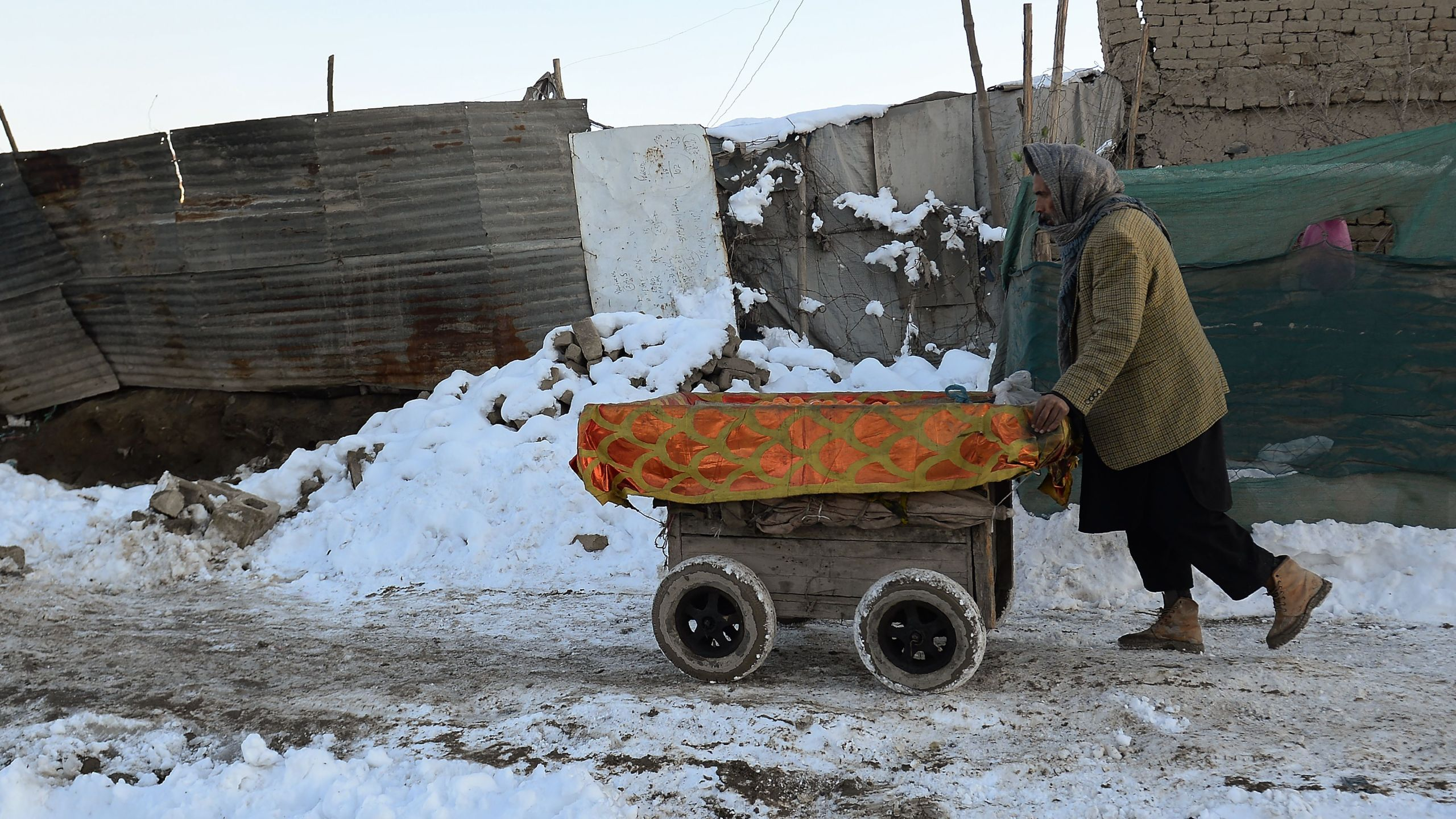 An Afghan fruit vendor pushes his cart along a roadside near the Eid Gah Mosque in Kabul on Jan. 6, 2019. (Credit: Shakib Rahmani/AFP/Getty Images)