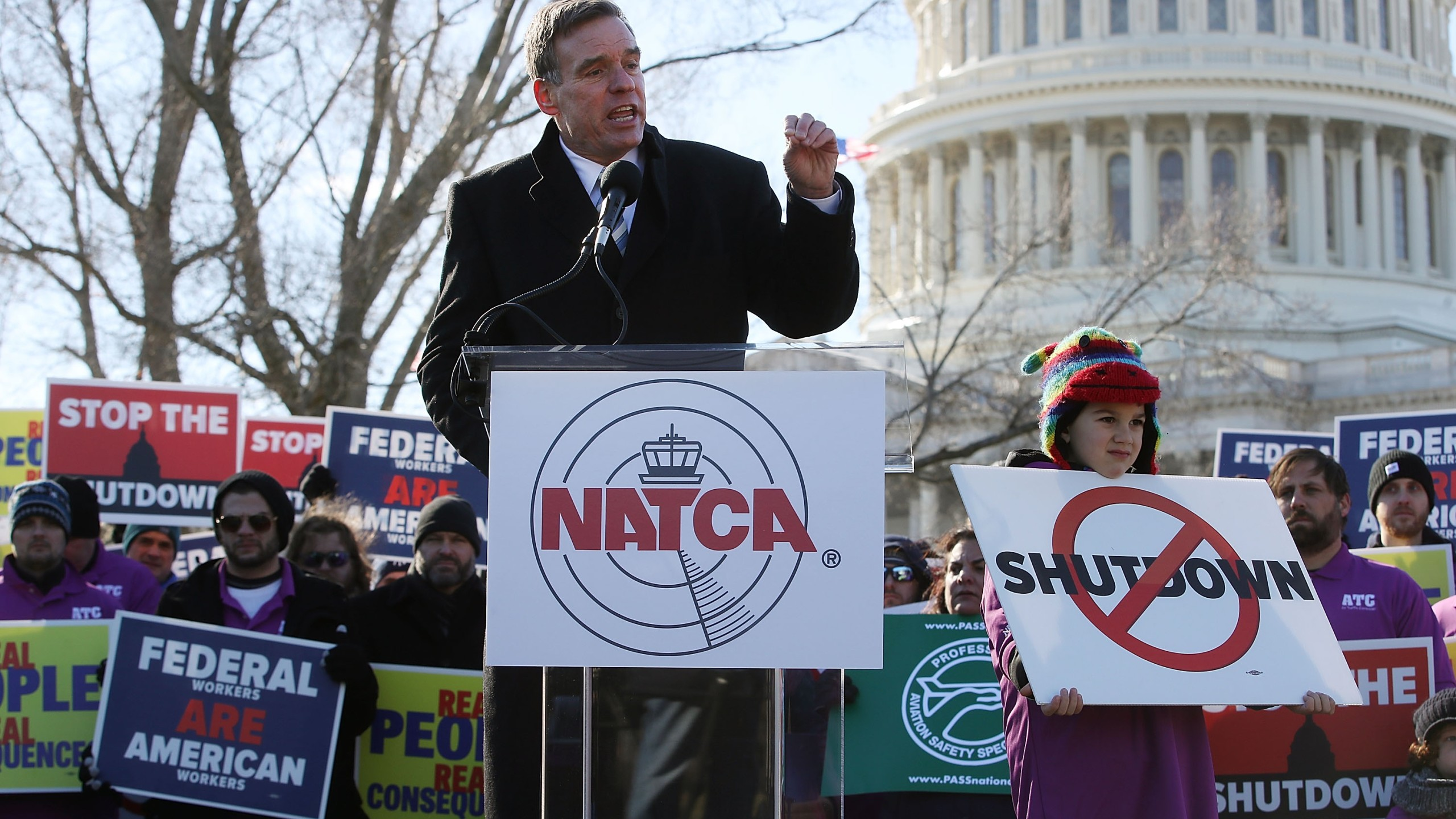 U.S. Sen. Mark Warner (D-VA) speaks while flanked by furloughed workers during a protest hosted by the National Air Traffic Controllers Association on Capitol Hill on Jan. 10, 2019. (Credit: Mark Wilson/Getty Images)