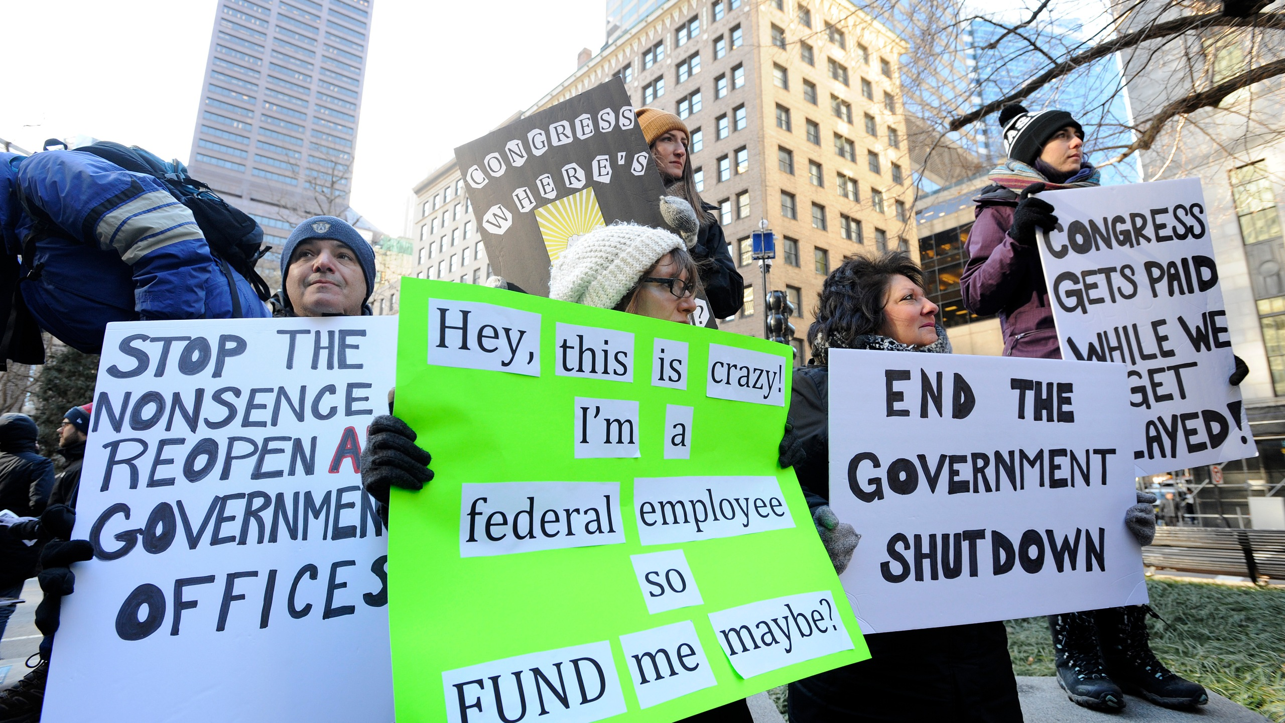 Demonstrator hold signs during a protest rally by government workers and concerned citizens against the government shutdown on Friday, Jan. 11, 2019. (Credit: Joseph Prezioso/AFP/Getty Images)