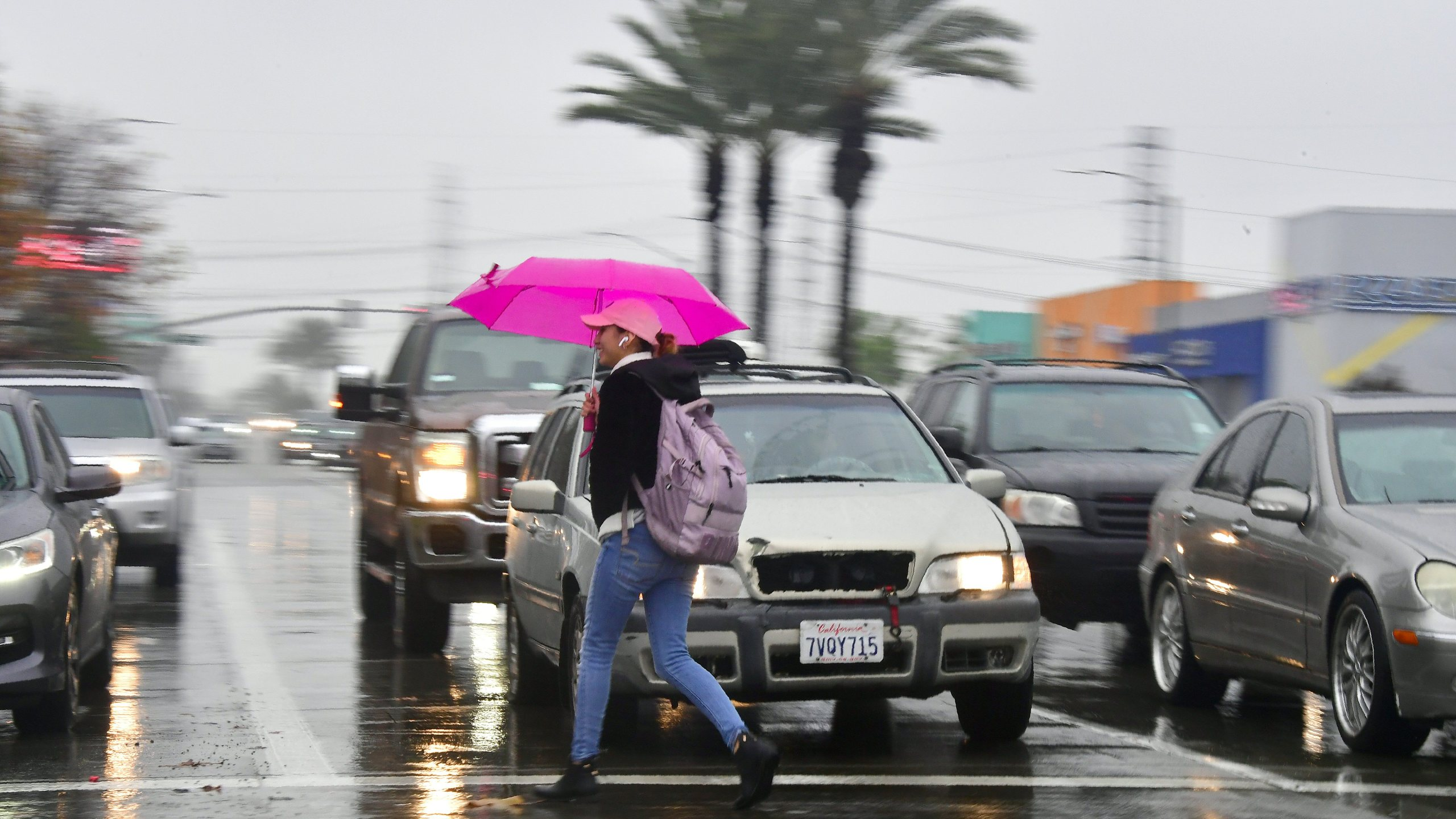 A pedestrian crosses a street in the rain in Montebello, California on January 16, 2019. (Credit: FREDERIC J. BROWN/AFP/Getty Images)