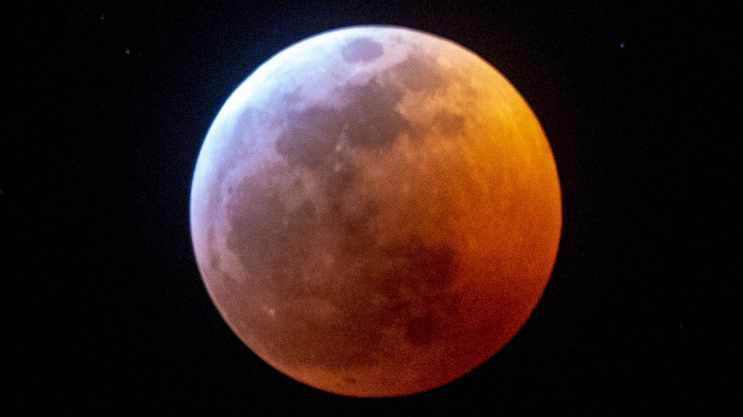 Earth's shadow almost totally obscures the view of the so-called Super Blood Wolf Moon during a total lunar eclipse, on Sunday January 20, 2019, in Miami. (Credit: GASTON DE CARDENAS/AFP/Getty Images)