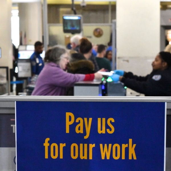"""A placard stating """"Pay us for our work"""" is displayed on a security line after Transportation Security Administration and other workers held a protest outside the Philadelphia International Airport on Jan. 25, 2019. (Credit: Mark Makela / Getty Images)"""
