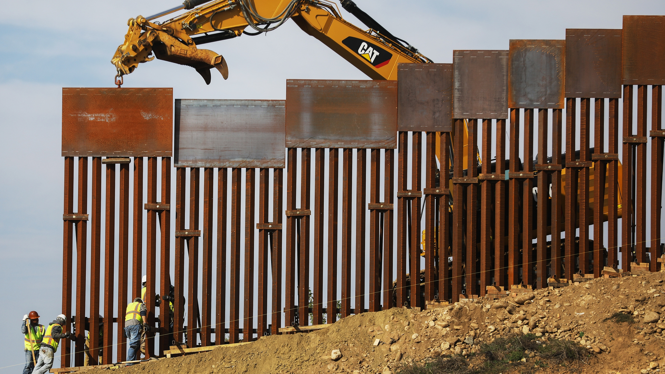 A construction crew installs new sections of the U.S.-Mexico border barrier replacing smaller fences on January 11, 2019 as seen from Tijuana, Mexico.. (Credit: Mario Tama/Getty Images)