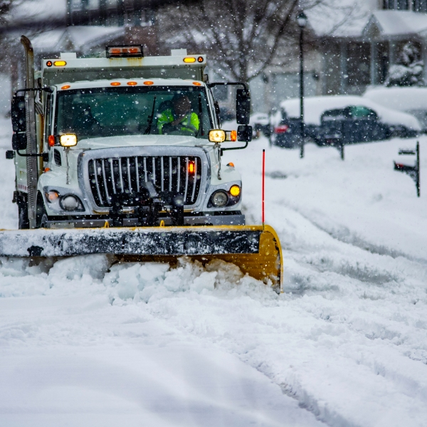 File photo of heavy equipment driver working to push snow to the side of the streets after a blizzard. (Credit: Getty Images)