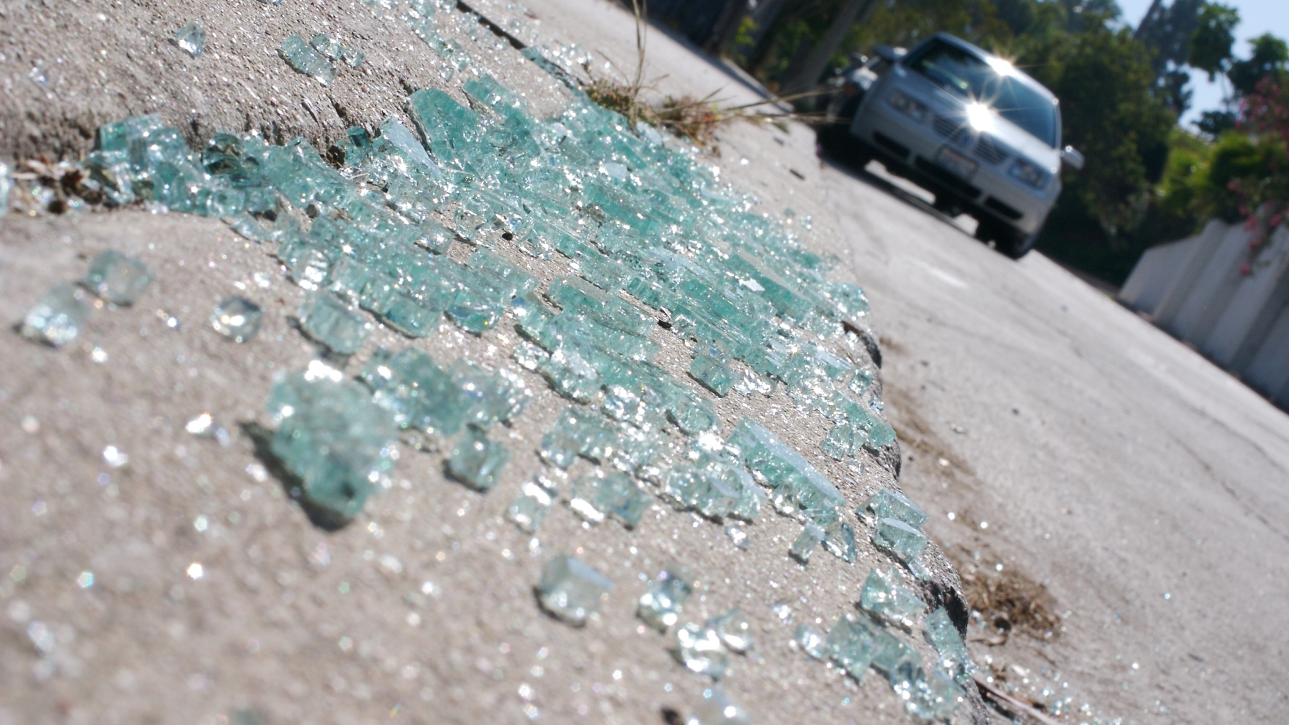 A file image shows broken glass on the curb with vehicles in the background. (Credit: iStock / Getty Images Plus)