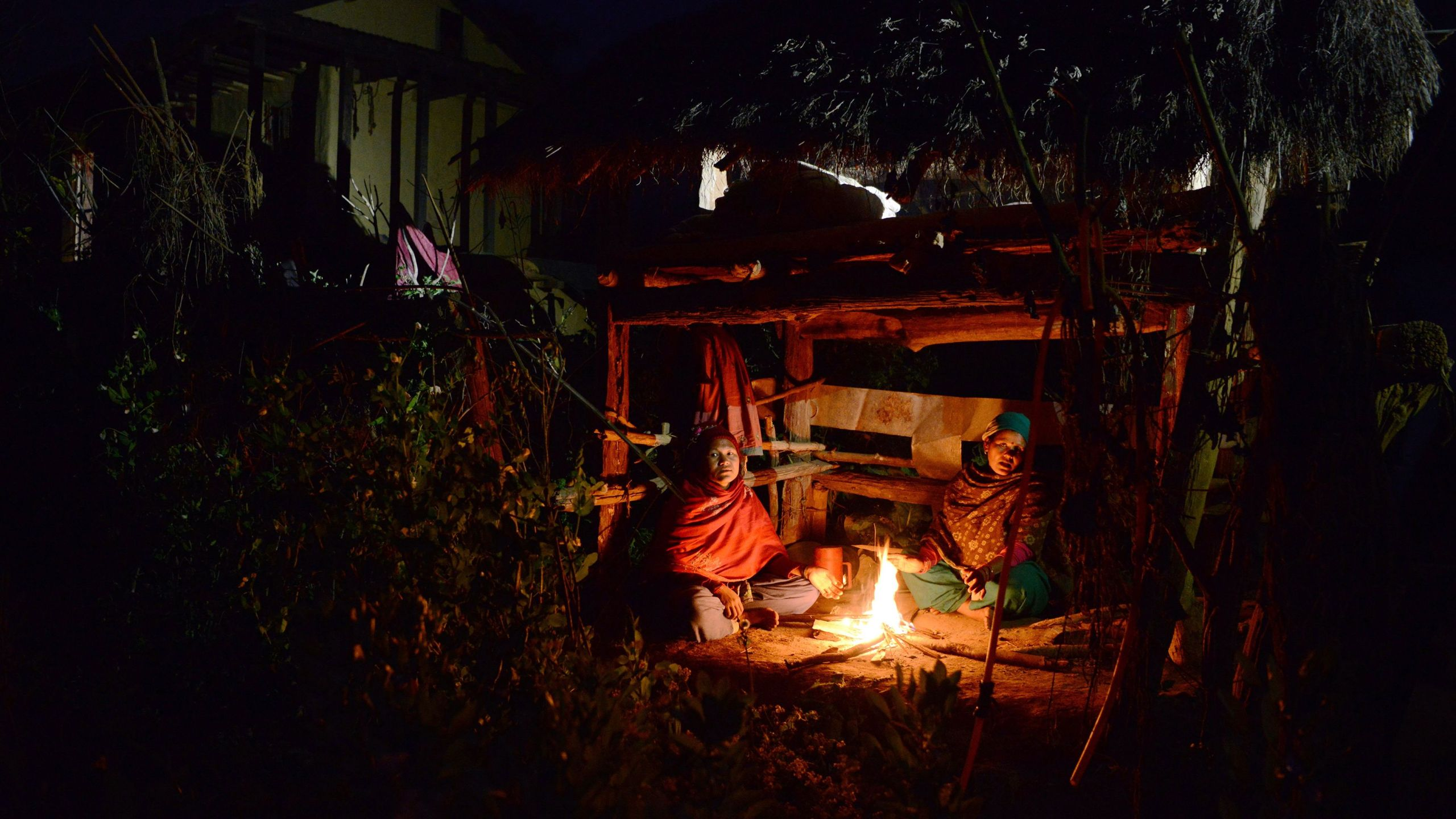 In this photograph taken on February 3, 2017, Nepalese women Pabitra Giri (L) and Yum Kumari Giri (R) sit by a fire as they live in a Chhaupadi hut during their menstruation period in Surkhet District, some 520km west of Kathmandu. The practice of banning women from the home when they are menstruating is linked to Hinduism and considers women untouchable at this time. They are banished from the home -- barred from touching food, religious icons, cattle and men -- and forced into a monthly exile sleeping in basic huts. (Credit: PRAKASH MATHEMA/AFP/Getty Images)