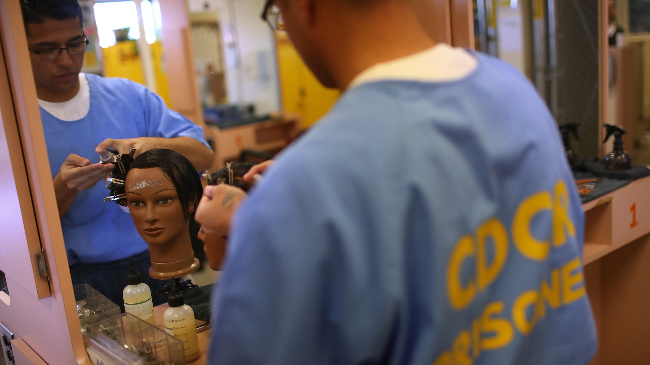 Inmate Cornelio Huerta practices grooming hair on a mannequin during a cosmetology class at Valley State Prison in Chowchilla on March 2, 2017. (Credit: Justin Sullivan / Getty Images)