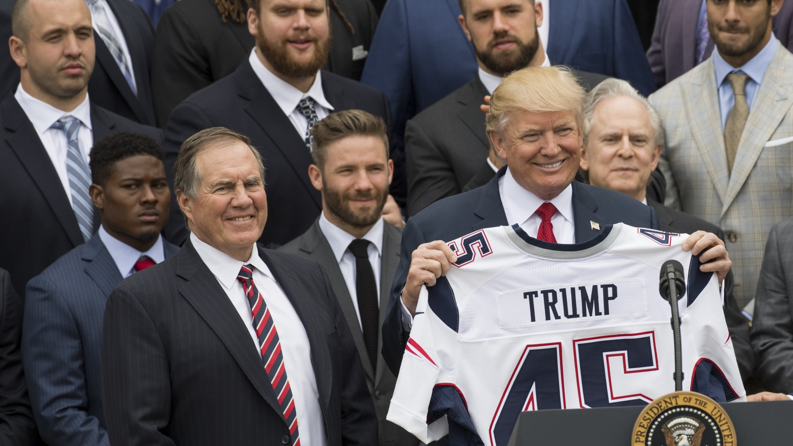 Donald Trump holds a jersey given to him by New England Patriots head coach Bill Belichick alongside members of the team during a ceremony honoring them as 2017 Super Bowl Champions on the South Lawn of the White House in Washington, D.C., on April 19, 2017. (Credit: SAUL LOEB/AFP/Getty Images)