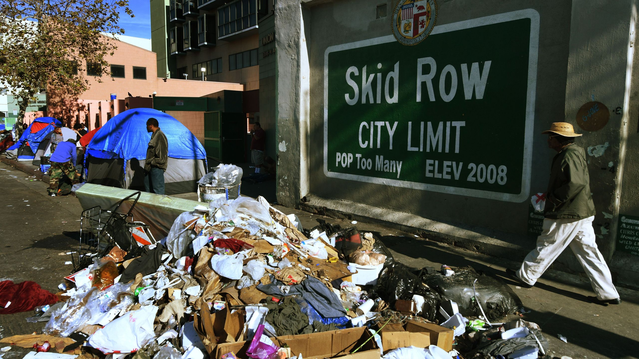 "Trash lies beside a mural that reads ""Skid Row City Limit"" during the annual homeless count in Los Angeles on Jan. 26, 2018."