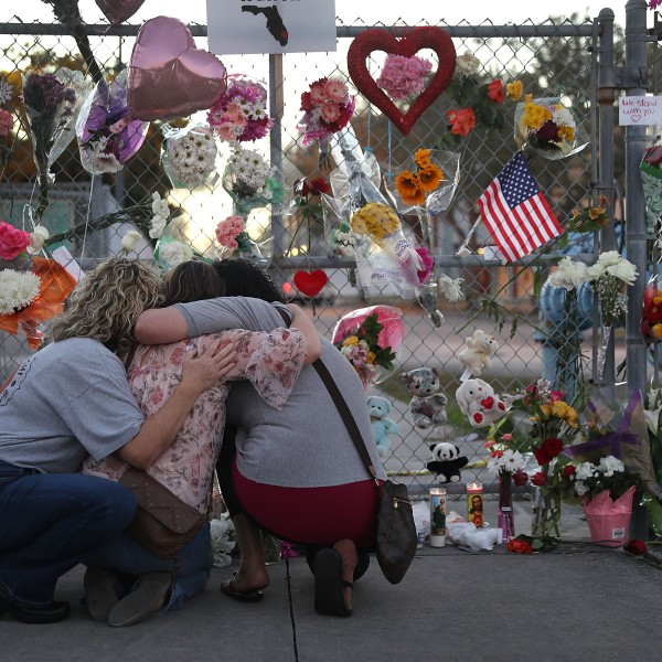 Shari Unger, Melissa Goldsmith and Giulianna Cerbono (from left) hug each other as they visit a makeshift memorial set up in front of Marjory Stoneman Douglas High School in Parkland, Florida, on Feb. 18, 2018. (Credit: Joe Raedle / Getty Images)