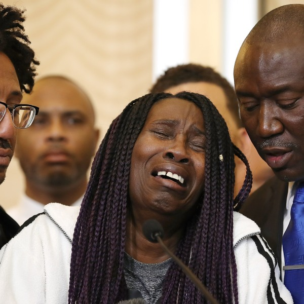 Sequita Thompson, center, the grandmother of Stephon Clark, cries as she speaks during a news conference with civil rights attorney Ben Crump, right, on March 26, 2018, in Sacramento. (Credit: Justin Sullivan / Getty Images)