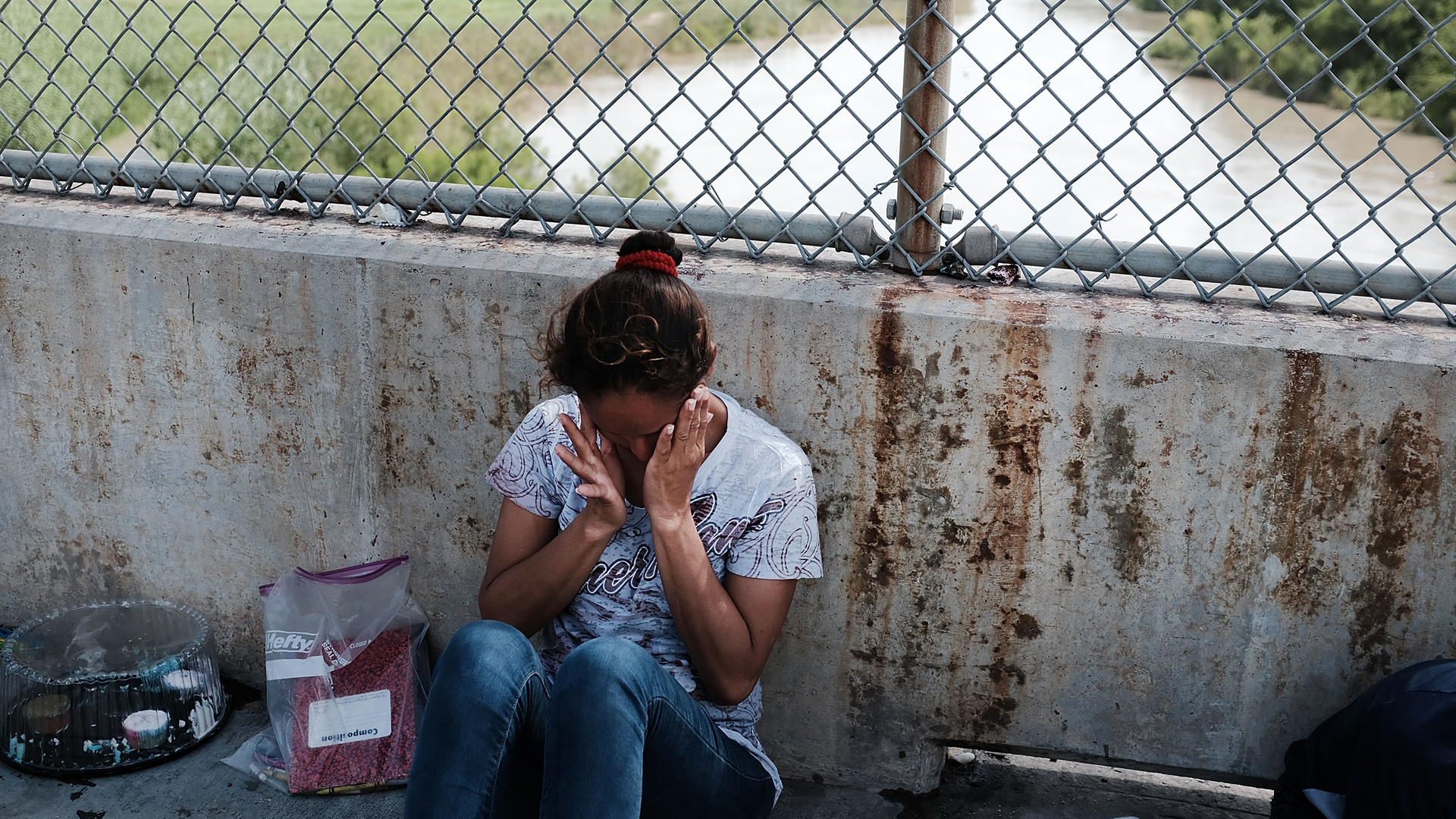 A Honduran woman, fleeing poverty and violence in her home country, waits along the border bridge after being denied entry into the U.S. from Mexico on June 25, 2018, in Brownsville, Texas. (Credit: Spencer Platt/Getty Images)