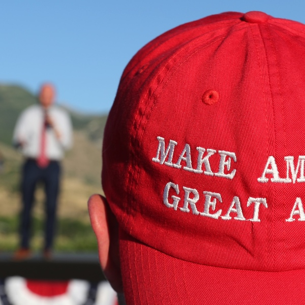 """A Romney supporter listens to a speaker as he wears a """"Make America Great Again"""" hat at the Mitt Romney election party on June 26, 2018 in Orem, Utah. (Photo by George Frey/Getty Images)"""