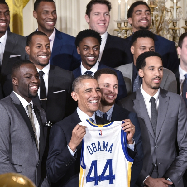 Then-President Obama holds a jersey as he poses with the 2015 NBA Champion Golden State Warriors during an event in their honor in the East Room of the White House on February 4, 2015. (Credit: MANDEL NGAN/AFP/Getty Images)