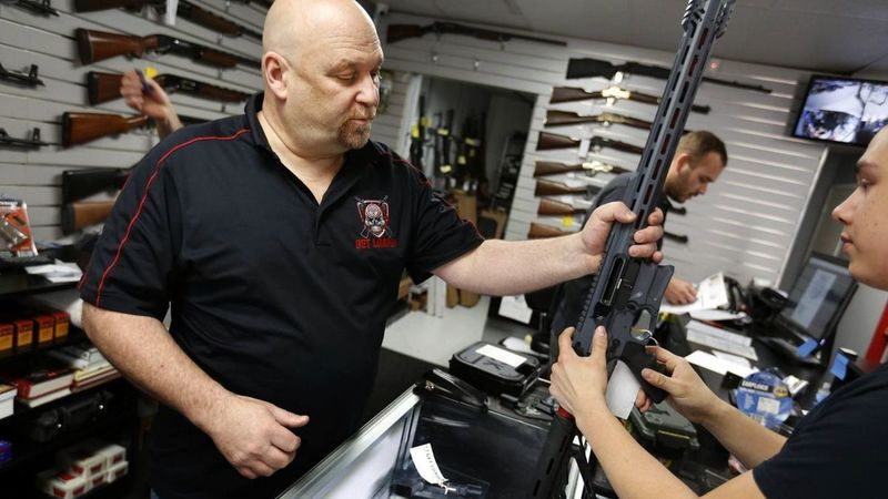 Terry McGuire, owner of the Get Loaded gun store in Grand Terrace in San Bernardino County, shows a customer a Cobalt Kinetics BAMF rifle in this undated photo. (Credit: Barbara Davidson / Los Angeles Times)