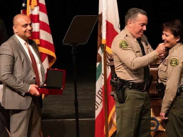Deputy Caren Carl Mandoyan looks on as L.A. County Sheriff Alex Villanueva places a pin on the collar of Asst. Sheriff Maria Gutierrez at Villanueva's swearing-in ceremony in December 2018. (Credit: Mel Melcon / Los Angeles Times)