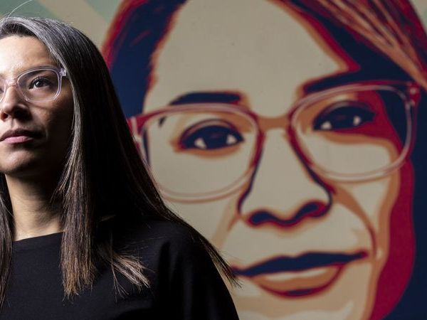 """Roxana Duenas, a Boyle Heights teacher of history and ethnic studies, stands before an image of her face that's been widely circulated across """"Stand with LA Teachers"""" posters during the strike in January 2019. (Credit: Kent Nishimura / Los Angeles Times)"""