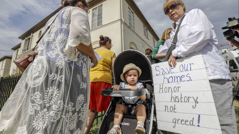 Aura Valenzuela, left, with her 15-month-old daughter Zoey Moran, watches tenants of the Las Palmas Courtyard Apartments, the Coalition to Preserve L.A. and others express opposition to the Crossroads Hollywood development, which was approved by the L.A. City Council on Jan. 22, 2019. (Credit: Irfan Khan / Los Angeles Times)