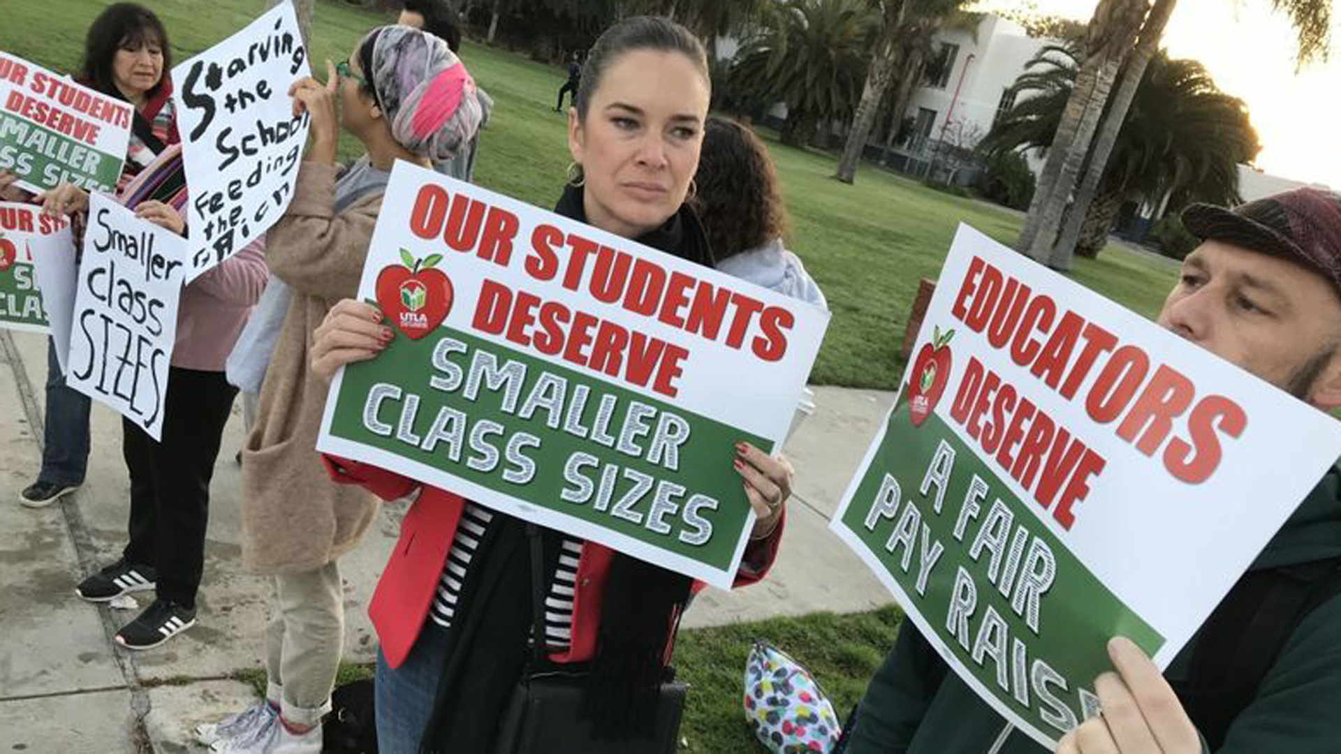 Timothy Hayes right, and Anastasia Foster, center, joined supporters of LAUSD teachers in front of Venice High School for a rally to show their solidarity with the educators and UTLA's call for lower class sizes Thursday morning. (Credit: Brian van der Brug / Los Angeles Times)