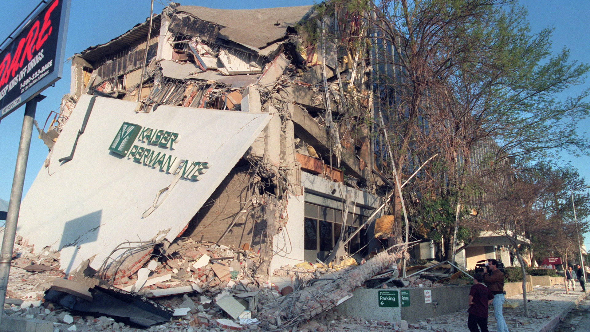 People survey the damage to the Kaiser Permanente Building following the Northridge earthquake on January 17, 1994. (Credit: HAL GARB/AFP/Getty Images)