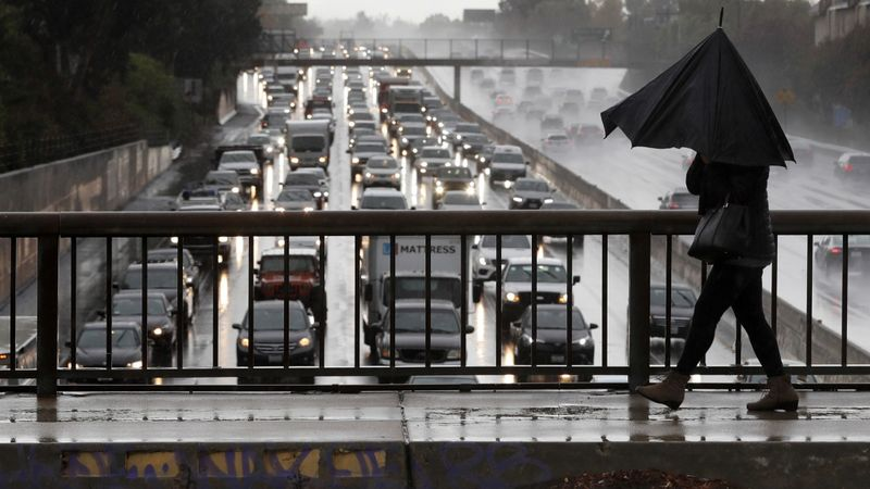 Nayer Shahram walks under a broken umbrella on Louise Avenue in Encino as traffic crawls along the 101 Freeway during a storm in December 2018. (Credit: Mel Melcon / Los Angeles Times)
