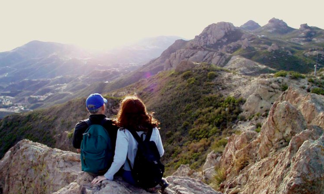 Hikers rest on a rock on a trail in the Santa Monica Mountains. (Credit: Santa Monica Mountains/ National Park Service)