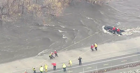 LAFD working to rescue a man who was clinging to a tree in the rain-swollen Los Angeles River near Griffith Park on Jan. 31, 2019. (Credit: KTLA)
