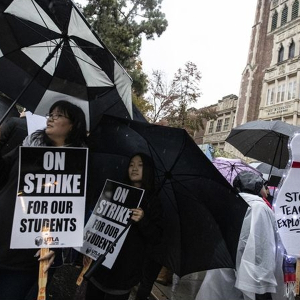 English magnet teacher Sarah Lee-Park, left, is among those holding signs and umbrellas at John Marshall High School on Monday morning. Her daughter Faith Park, 13, joined her on the picket line. (Credit: Brian van der Brug / Los Angeles Times)