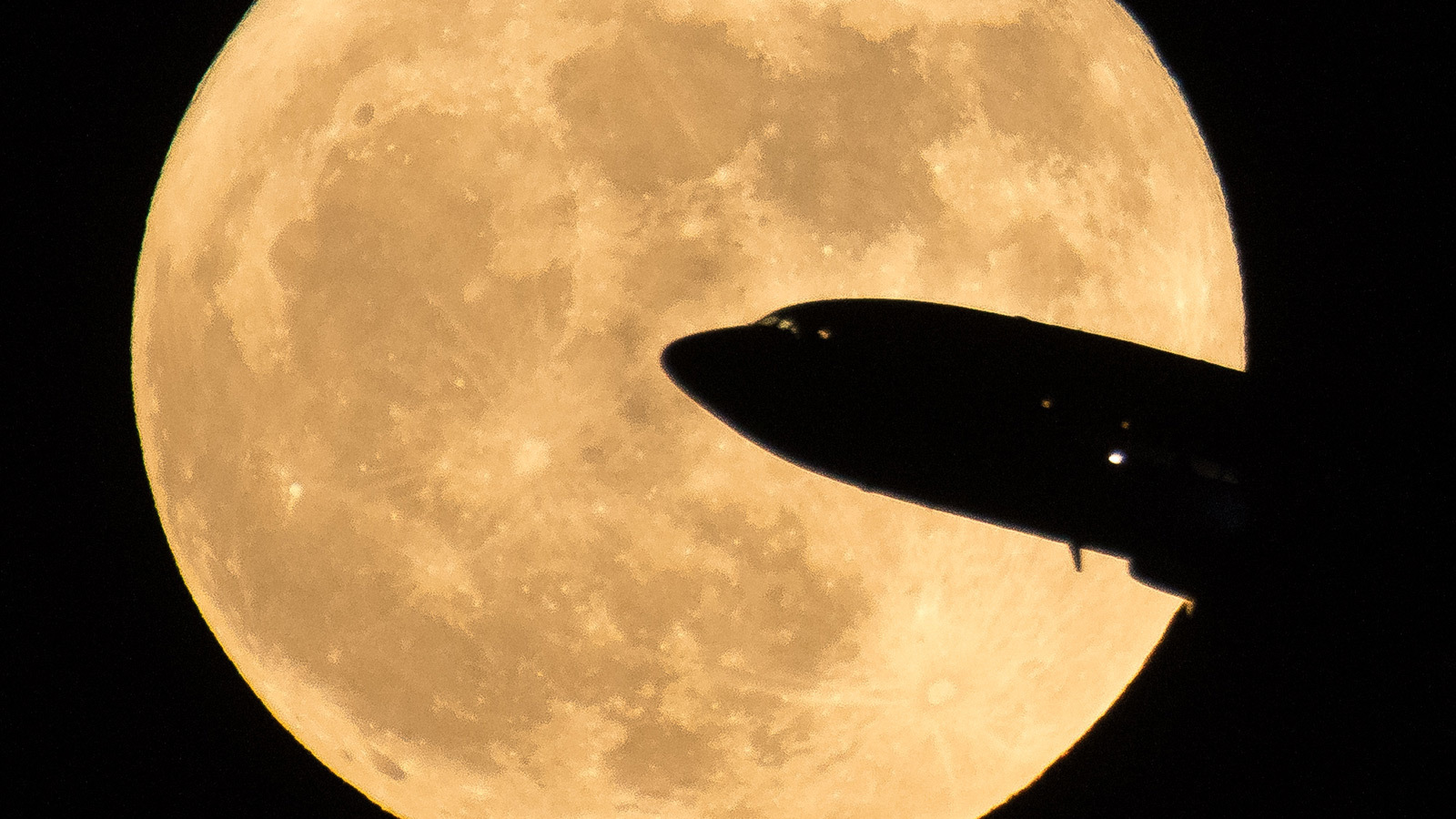 An aircraft taking off from Ronald Reagan National Airport is seen passing in front of the full moon as it rises, Sunday, Dec. 3, 2017 in Washington. (Credit: NASA/Bill Ingalls