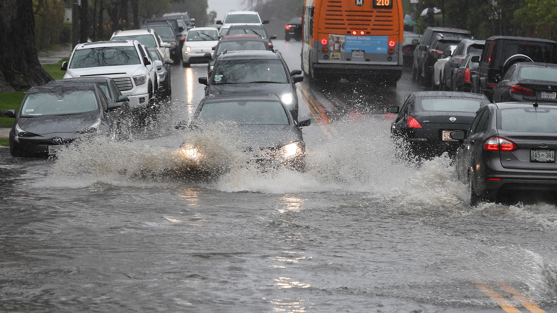 Cars drive through a flooded street after a storm dumped heavy rain on Los Angeles on February 2, 2019. (Credit: MARK RALSTON/AFP/Getty Images)