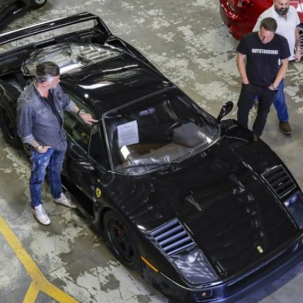 The owner of Gas Monkey Garage and TV personality Richard Rawlings, left, Dennis Collins and his cohost Russel Holmes check out a 1991 Ferrari F40 at Apple Auctioneering Co., which manages government assets and auctions them off online. The vehicle ended up selling for $760,000. (Irfan Khan / Los Angeles Times)