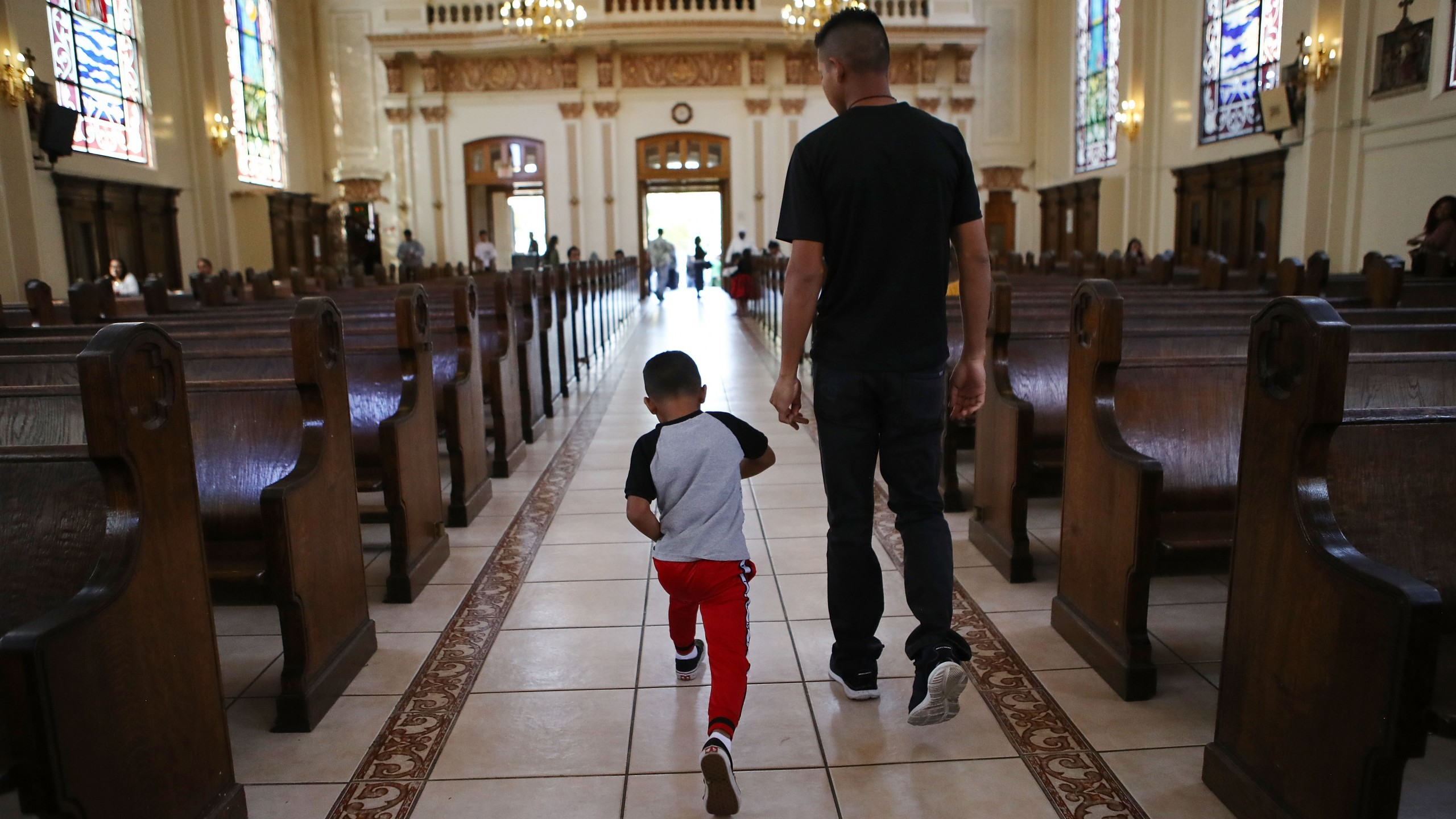"""Honduran father Juan and his six-year-old son Anthony depart after attending Sunday Mass on Sept. 9, 2018, in Oakland. They fled their country, leaving many family members behind, and crossed the U.S. border in April at a lawful port of entry in Brownsville, Texas seeking asylum. They were soon separated and spent the next 85 days apart in detention. Juan was sent to Tulsa, Oklahoma, while his son was sent to a detention shelter in New York. They were one of almost 2,600 families separated due to the Trump administration's """"zero tolerance"""" immigration policy. (Credit: Mario Tama/Getty Images)"""