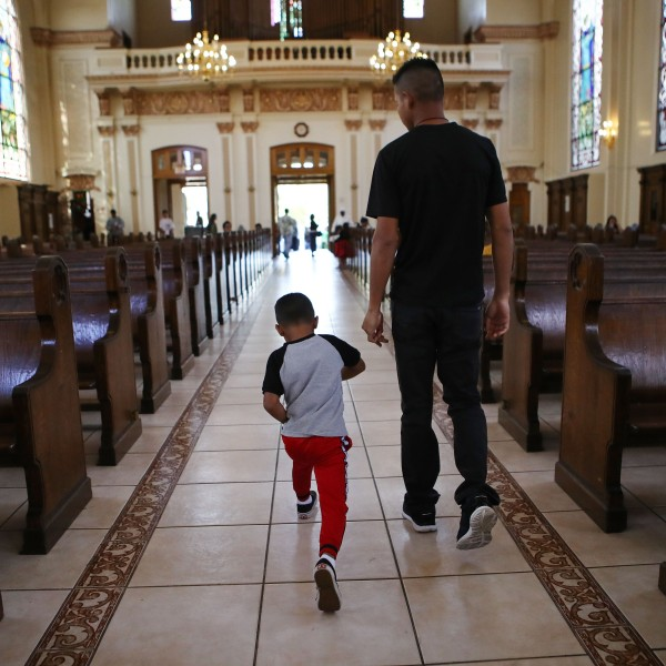 "Honduran father Juan and his six-year-old son Anthony depart after attending Sunday Mass on Sept. 9, 2018, in Oakland. They fled their country, leaving many family members behind, and crossed the U.S. border in April at a lawful port of entry in Brownsville, Texas seeking asylum. They were soon separated and spent the next 85 days apart in detention. Juan was sent to Tulsa, Oklahoma, while his son was sent to a detention shelter in New York. They were one of almost 2,600 families separated due to the Trump administration's ""zero tolerance"" immigration policy. (Credit: Mario Tama/Getty Images)"