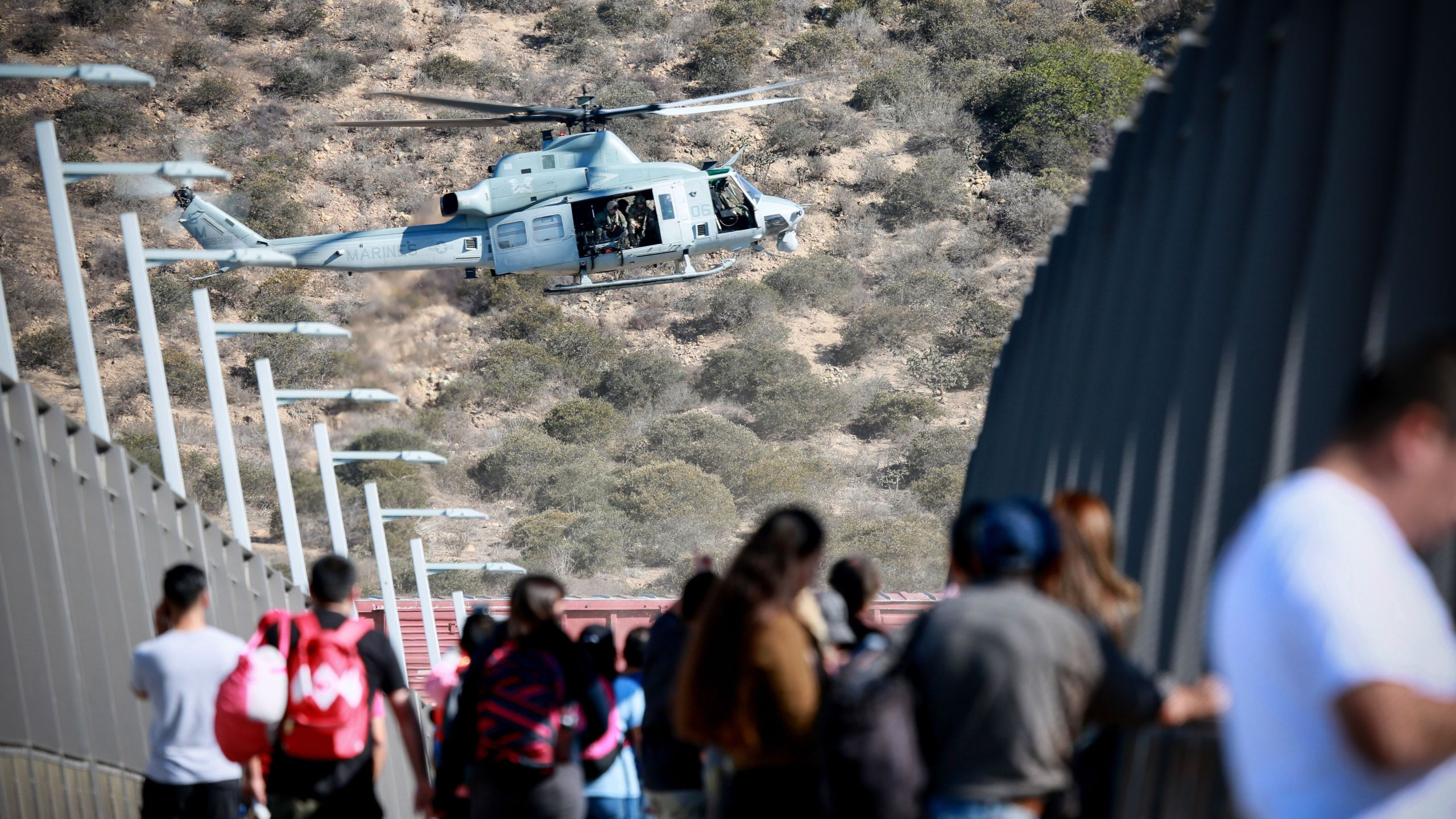 A U.S. military helicopter flies past a pedestrian bridge at the San Ysidro border crossing point south of San Diego after the closing of the U.S.-Mexico border was ordered on Nov. 25, 2018. (Credit: Sandy Huffaker / AFP / Getty Images)