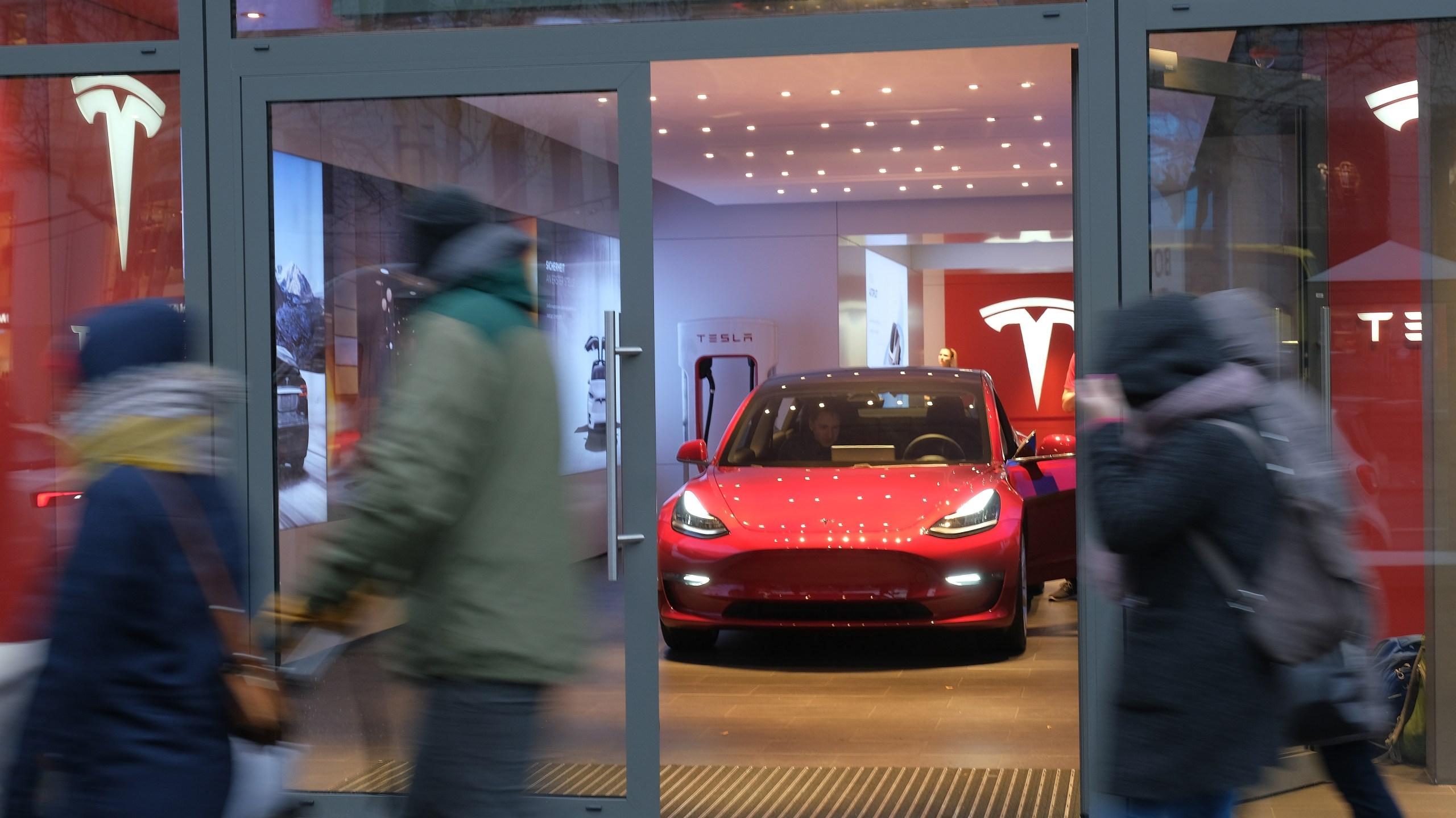 People walk past a Tesla dealership on in Berlin, Germany, on Jan. 4, 2019. (Credit: Sean Gallup / Getty Images)