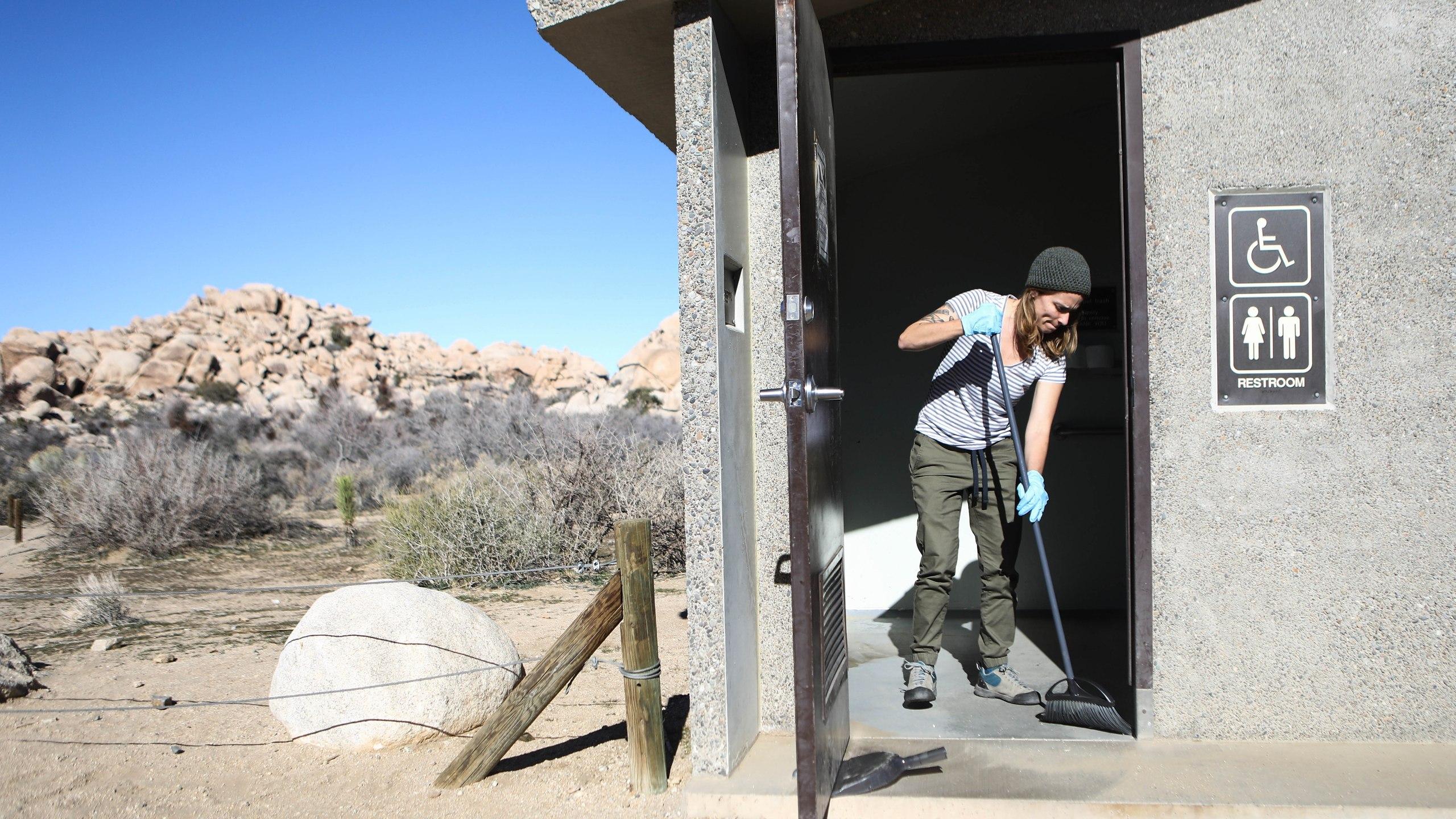 Volunteer Alexandra Degen cleans a restroom at Joshua Tree National Park on January 4, 2019 in Joshua Tree National Park, California. (Credit: Mario Tama/Getty Images)