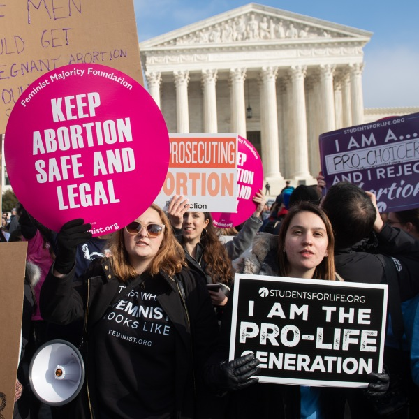 Abortion-rights activists hold signs alongside anti-abortion activists participating in the March for Life, an annual event to mark the anniversary of the 1973 case Roe v. Wade, outside the Supreme Court of the United States on Jan. 18, 2019. (Credit: Saul Loeb / AFP / Getty Images)