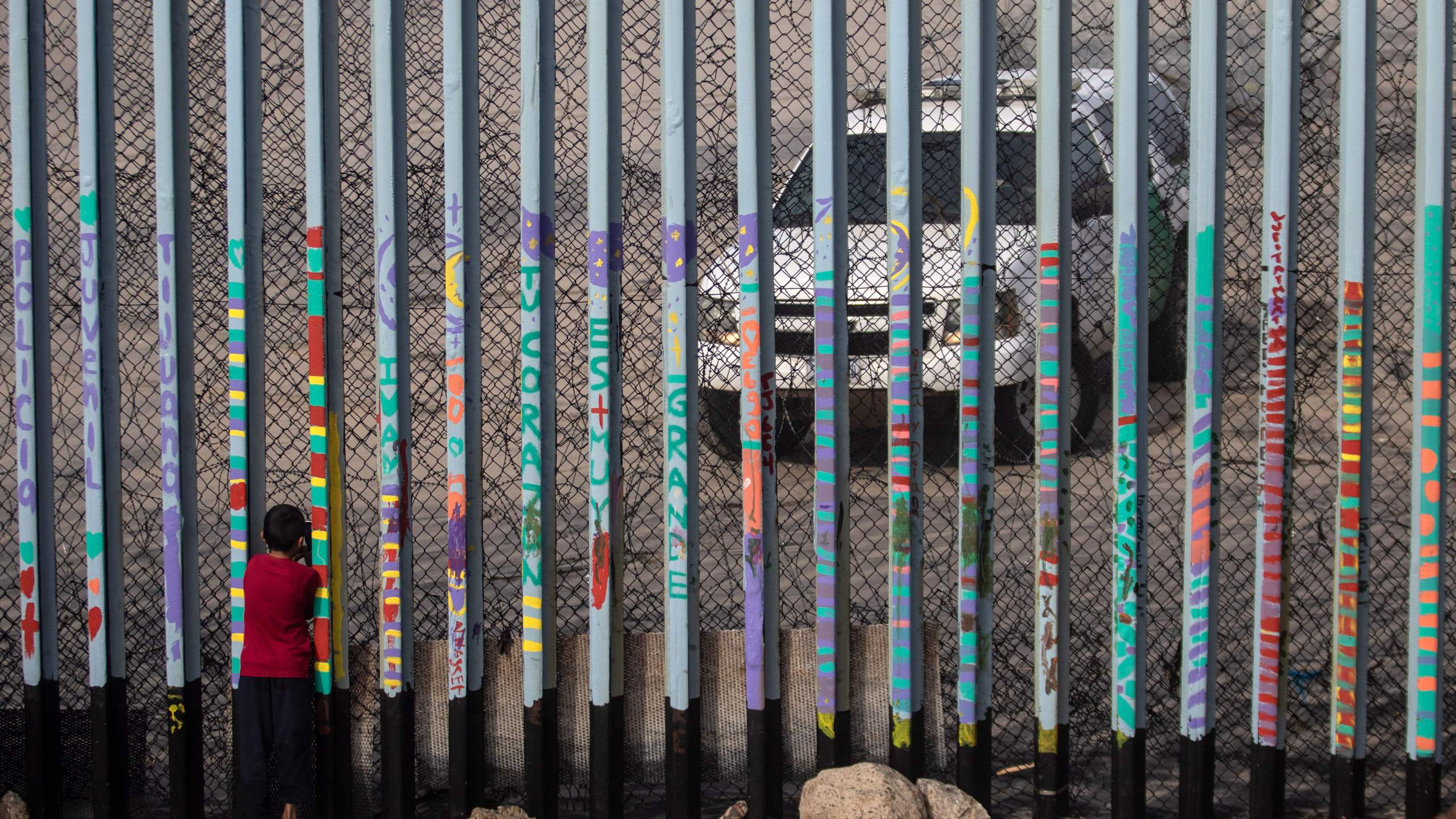 A boy looks at U.S. border patrol guards through the US-Mexico border fence, in Tijuana, in Baja California State, Mexico, on Jan. 18, 2019. (Credit: GUILLERMO ARIAS/AFP/Getty Images)