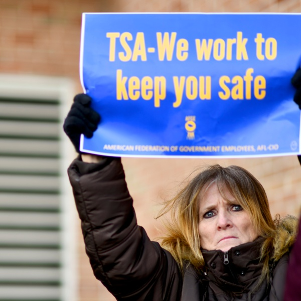 """Elizabeth Hughes holds a placard stating """"TSA- We work to keep you safe"""" while demonstrating with Philadelphia Airport TSA and airport workers outside the Philadelphia International Airport on January 25, 2019 in Philadelphia, Pennsylvania. (Credit: Mark Makela/Getty Images)"""