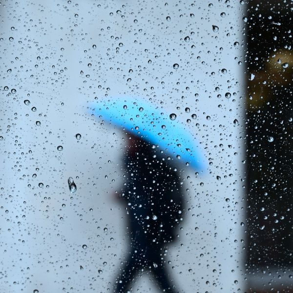 Raindrops are seen on a vehicle window as a pedestrian walks in the rain in Los Angeles, California on Jan. 31, 2019, as heavy rains hit Southern California. (Credit: FREDERIC J. BROWN/AFP/Getty Images)