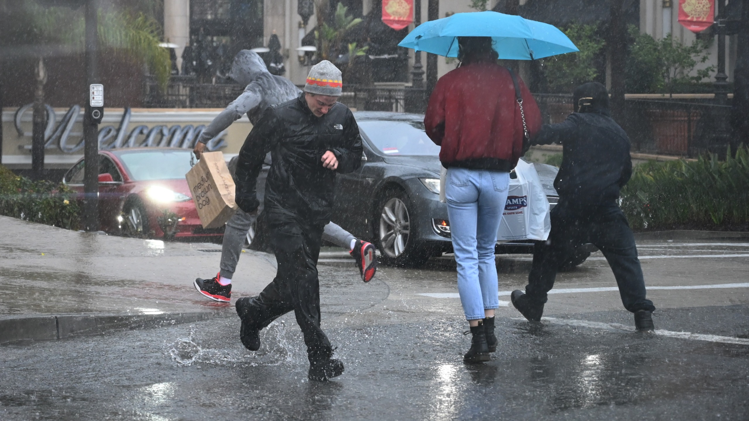 People run through water flooding a street in Glendale on Feb. 2, 2019. (Credit: ROBYN BECK/AFP/Getty Images)
