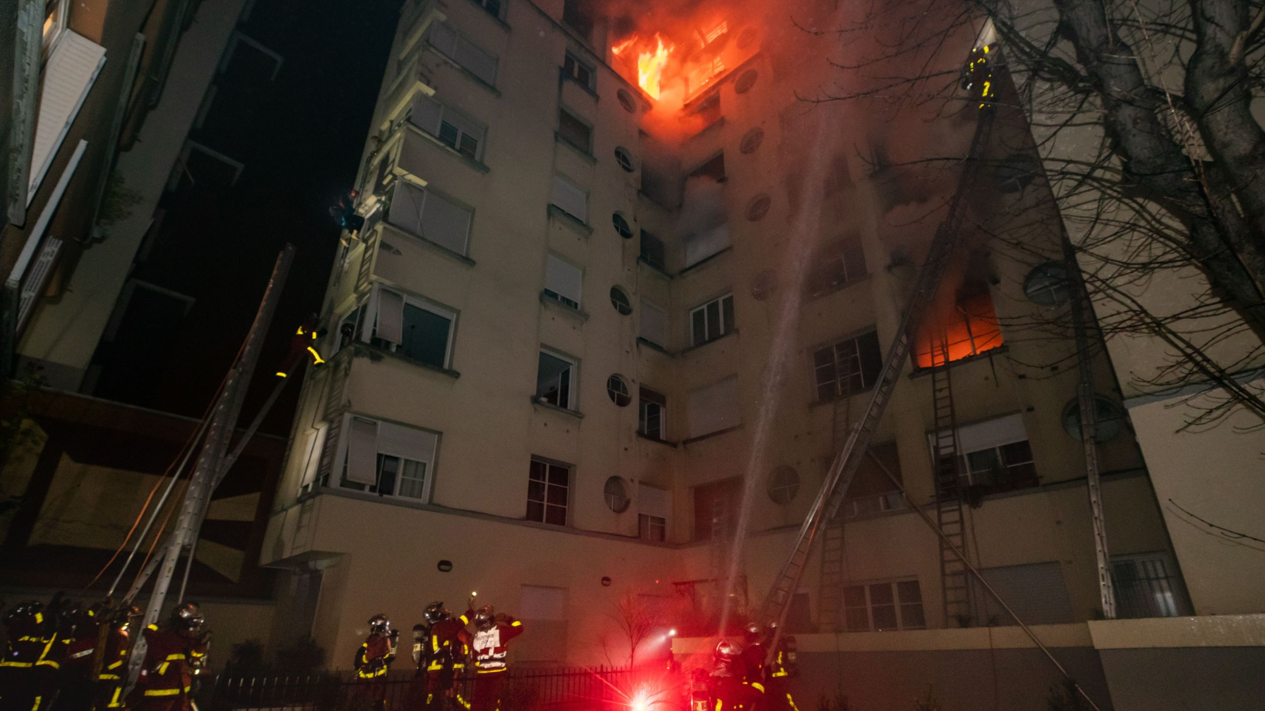 This handout picture taken and released by the Paris firefighters brigade (BSPP) in the night of February 5, 2019 shows firemen spraying water as a fire burns in a building in Erlanger street in the 16th arrondissement in Paris. (Credit: BENOIT MOSER/AFP/Getty Images)