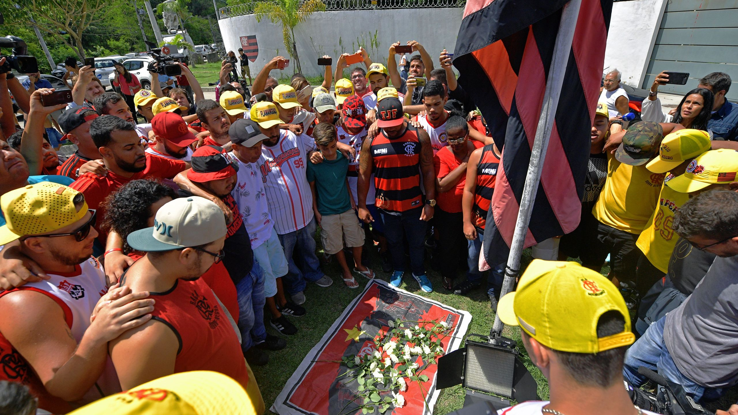 Brazilian football club Flamengo fans gather to lay flowers at the entrance of the club's training center after a deadly fire in Rio de Janeiro, Brazil, on Feb. 8, 2019. (Credit: Carl De Souza / AFP / Getty Images)