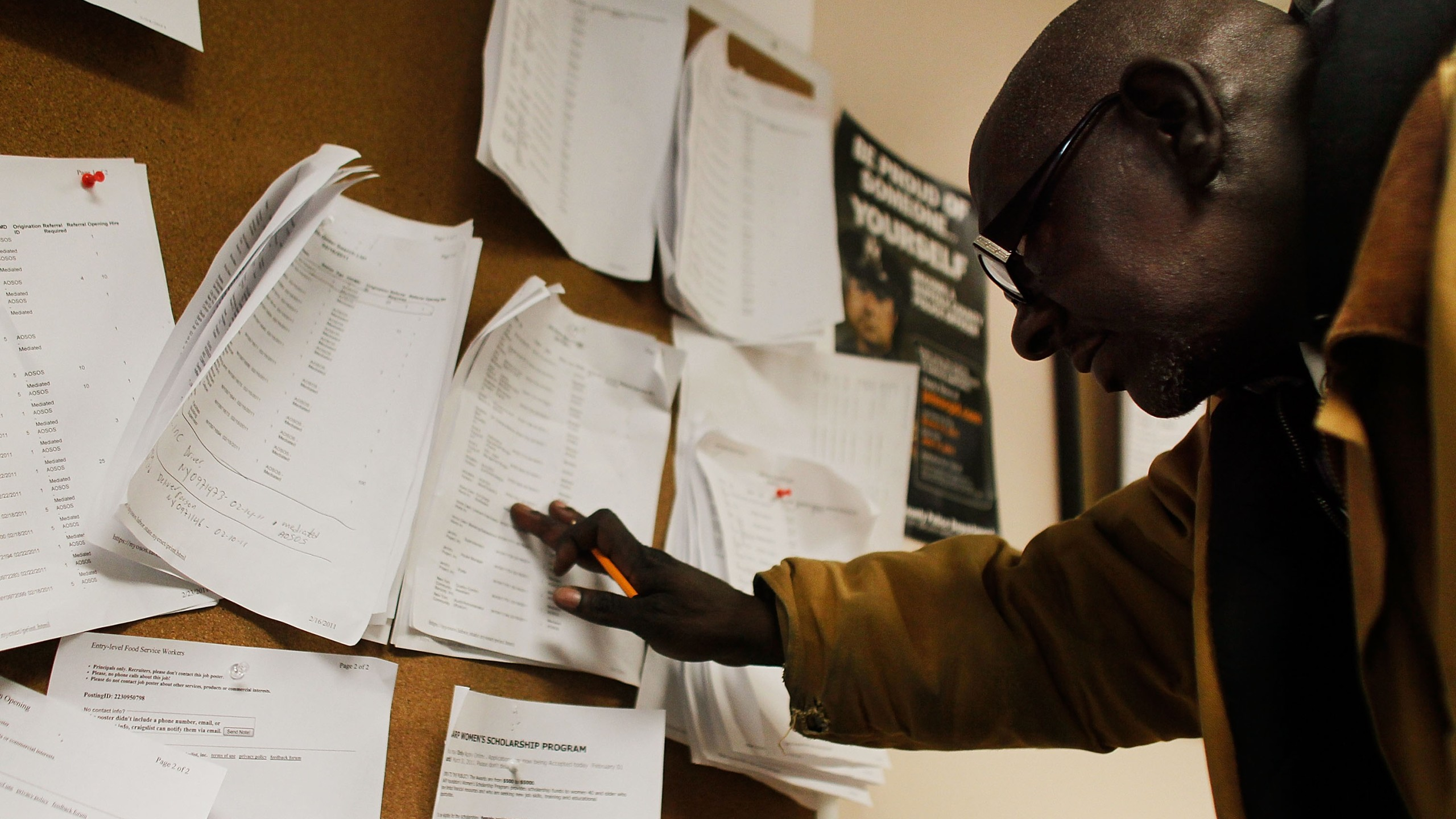 An unemployed man looks over job listings on a board at a New York State Department of Labor Employment Services office on March 3, 2011. (Credit: Chris Hondros/Getty Images)