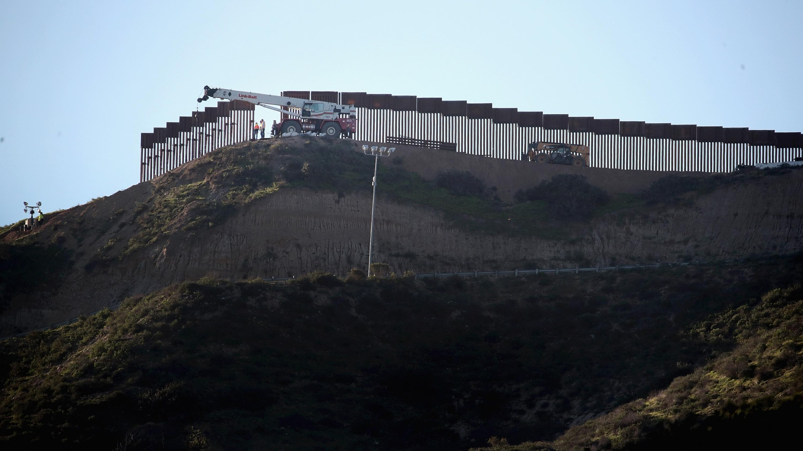 Workers construct a barrier between the United States and Mexico in San Diego County on Jan. 23, 2019. (Credit: Scott Olson / Getty Images)