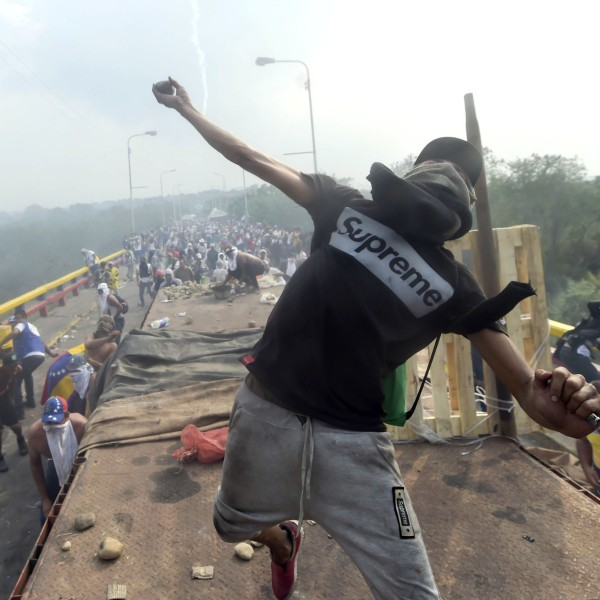 Demonstrators throw stones in clashes with the security forces at the Francisco de Paula Santander international bridge Bridge linking Cucuta, Colombia, and Urena, Venezuela, during an attempt to cross humanitarian aid over the border into Venezuela, on Feb. 23, 2019. (Credit: RAUL ARBOLEDA/AFP/Getty Images)