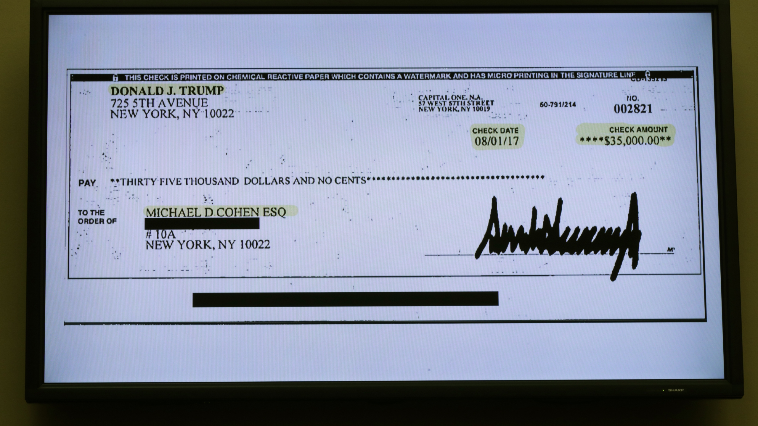 A copy of a check paid to Michael Cohen by President Trump is displayed as Cohen, former attorney and fixer for Trump testifies before the House Oversight Committee on Capitol Hill February 27, 2019 in Washington, DC. (Credit: Chip Somodevilla/Getty Images)